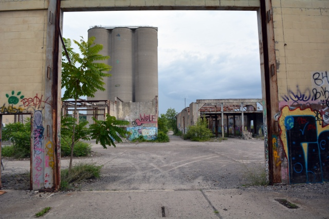 Looking out from abandoned building toward concrete silos and other abandoned buildings